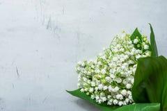 Petit bouquet des fleurs du muguet avec des feuilles de vert sur le fond de Grey Stone Concrete Cement Metal Anniversaire de mari photographie stock libre de droits