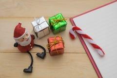Petit cadeau, petit père noël et carnet vide sur le backgr en bois Photo stock