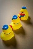 Petit caneton trois en caoutchouc jaune (direction) Photos libres de droits