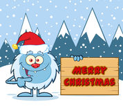 Petit caractère heureux de mascotte de bande dessinée de yeti avec Santa Hat Pointing To un signe en bois de Joyeux Noël Images libres de droits