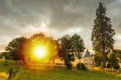 Petit château caché pendant le coucher du soleil sur un paysage idyllique image stock
