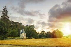 Petit château caché pendant le coucher du soleil sur un paysage idyllique photo libre de droits