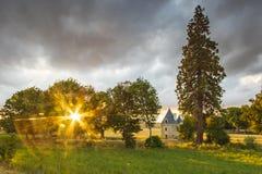 Petit château caché pendant le coucher du soleil sur un paysage idyllique image libre de droits