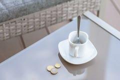Petit changement dans un euro et une tasse de café vide sur une table en verre de café extérieur Paiement, astuce images stock