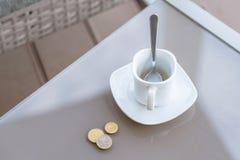 Petit changement dans un euro et une tasse de café vide sur une table en verre de café extérieur Paiement, astuce photos libres de droits