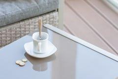 Petit changement dans un euro et une tasse de café vide sur une table en verre de café extérieur Paiement, astuce photographie stock