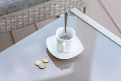 Petit changement dans un euro et une tasse de café vide sur une table en verre de café extérieur Paiement, astuce image libre de droits
