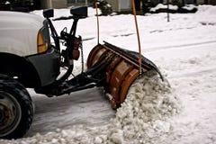 Petit chasse-neige enlevant la neige sur une rue de ville Images libres de droits