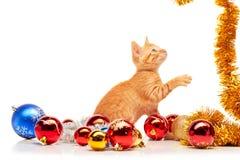 Petit chaton rouge mignon jouant avec la tresse d'or près des jouets colorés et scintillants de Noël Photos libres de droits