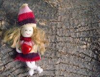 Petit chiffre de marionnette d'enfants, tenant le coeur sur le fond en bois approximatif d'écorce avec l'espace de copie Poupée f Photographie stock