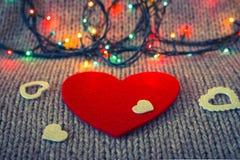 Petit coeur décoratif blanc sur un coeur rouge de feutre Photographie stock