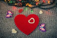 Petit coeur décoratif blanc sur un coeur rouge de feutre Images stock