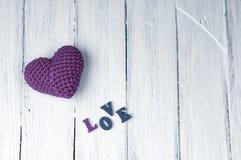 Petit coeur rouge avec l'amour de mot sur une surface en bois blanche Image libre de droits