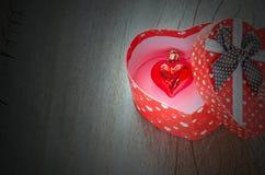 Petit coeur rouge dans le boîte-cadeau rouge de forme de coeur Images stock
