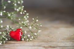 Petit coeur rouge des fleurs en verre et blanches sur un en bois rustique Photos libres de droits