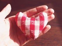 Petit coeur rouge et blanc mou dans la main ouverte Image libre de droits