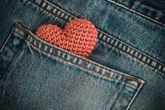Petit coeur tricoté dans la poche arrière de jeans Images libres de droits