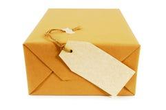 Petit colis ou paquet de papier brun avec le label vide d'isolement sur le fond blanc, vue de fin image libre de droits
