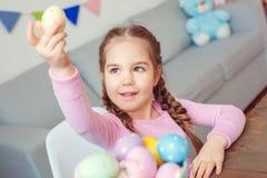 Petit concept mignon de célébration de Pâques de fille à la maison se reposant tenant l'oeuf  images stock
