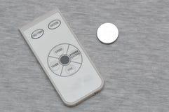 Petit contrôleur à distance blanc et gris et une batterie au lithium de pièce de monnaie de cellules de bouton Photographie stock
