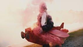 Petit costume pilote plat de port de sourire heureux d'amusement de fille avec des verres entourés par la fumée de couleur en deh banque de vidéos