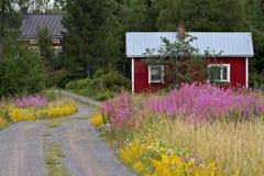 Petit cottage d'été par la route de campagne Photos libres de droits