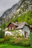 Petit cottage dans les Alpes avec un arbre Image libre de droits