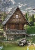 Petit cottage en bois avec un bateau Photos libres de droits