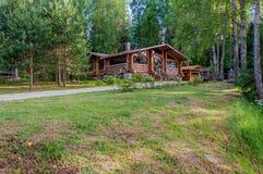 Petit cottage moderne de rondin sur la colline dans une forêt de pin Photographie stock libre de droits