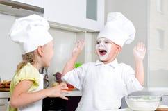 Petit cuisson heureuse de garçon et de fille dans la cuisine Photographie stock libre de droits