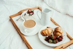 Petit déjeuner à la maison confortable dans le lit dans l'intérieur blanc de chambre à coucher Photographie stock