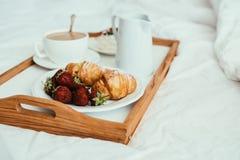 Petit déjeuner à la maison confortable dans le lit dans l'intérieur blanc de chambre à coucher Photographie stock libre de droits