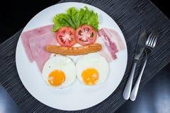 Petit déjeuner américain avec le lard et la saucisse de jambon d'oeufs Photographie stock