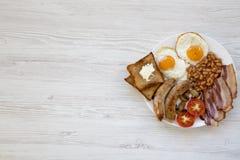 Petit déjeuner anglais avec des oeufs au plat, des saucisses, des haricots, le lard et des pains grillés au-dessus du fond en boi Photos libres de droits