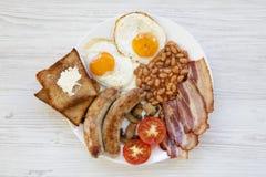 Petit déjeuner anglais avec des oeufs au plat, des saucisses, des haricots, le lard et des pains grillés sur le fond en bois blan Photographie stock