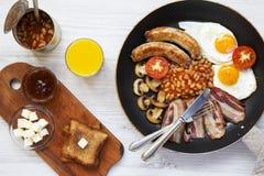 Petit déjeuner anglais dans une casserole avec les oeufs au plat, le lard, les saucisses, les haricots et les pains grillés sur l Photos libres de droits
