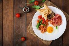 Petit déjeuner anglais - oeuf au plat, haricots, tomates, champignons, lard et pain grillé Photo stock