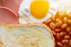 Petit déjeuner anglais : oeuf au plat, lard, haricots et pain grillé Images libres de droits