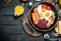 Petit déjeuner anglais traditionnel avec les oeufs au plat, le lard et les haricots rouges photos stock
