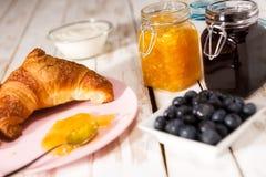 Petit déjeuner avec le croissant au-dessus d'une table en bois Images stock