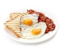 Petit déjeuner avec les oeufs au plat, le lard et les pains grillés Photographie stock libre de droits