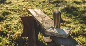 Petit déjeuner avec un livre en plein air Vapeur au-dessus d'une tasse thermo Ouvrez le livre sur la nature Livre et café potable photo stock