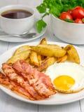 Petit déjeuner chaleureux avec le lard, l'oeuf au plat et la pomme de terre photos libres de droits