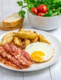 Petit déjeuner chaleureux avec le lard, l'oeuf au plat, la pomme de terre et les légumes photographie stock