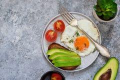 Petit déjeuner classique : grillez avec l'avocat, l'oeuf et les légumes sur le C.A. Images libres de droits