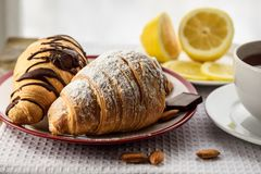Petit déjeuner, croissants sur la table, citron, thés d'amande photos libres de droits