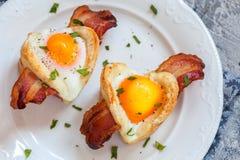 Petit déjeuner cuit au four d'oeufs avec la forme de coeur de lard pour le Saint Valentin Images libres de droits
