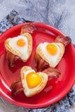 Petit déjeuner cuit au four d'oeufs avec la forme de coeur de lard pour le Saint Valentin Photos libres de droits