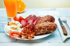 Petit déjeuner délicieux avec des oeufs au plat, des petits pains, le lard et le jambon sur un pl Photographie stock libre de droits