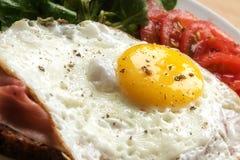 Petit déjeuner d'oeuf au plat avec du jambon, la salade verte et des tomates, fin  Image stock